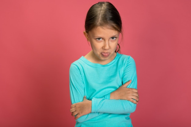 Маленькая красивая девочка на розовом фоне яркая одежда желтые штаны бирюзовая синяя рубашка обиделась и смотрит из-под бровей и показывает язык