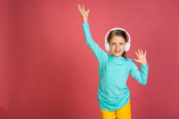小さな美しい女の赤ちゃんピンクの背景明るい服黄色のズボンターコイズブルーのシャツ白いヘッドフォンを身に着けている音楽とダンスを聴いて