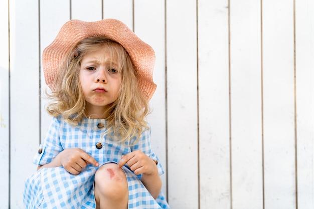 Маленькая красивая блондинка грустно со сломанным коленом на белом деревянном фоне