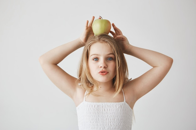Little beautiful blonde-haired girl in white dress holding apple on head with hands, , making funny face expressions, having fun.