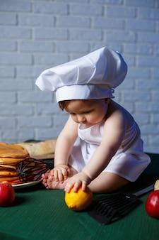 エプロン、子供たちの料理の衣装に身を包んだ小さな美しい子供。テーブルの上のパンケーキと焼きたてのペストリー。
