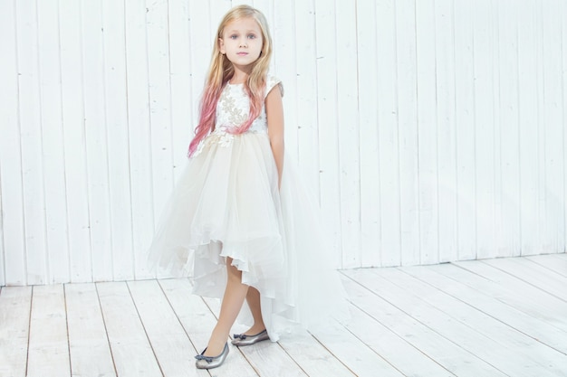 Little beautiful child girl in beautiful dress on white wooden background