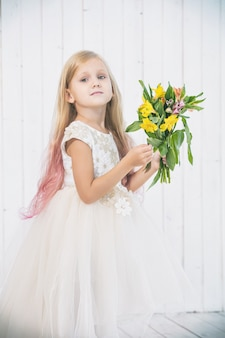 Little beautiful child girl in beautiful dress with bouquet of flowers on white wooden background