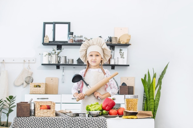 Little beautiful child girl cook in the kitchen with different vegetables and spaghetti