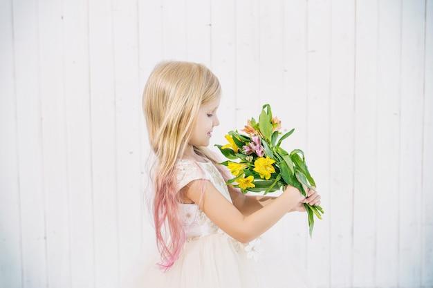 白い木製の背景に花の花束と美しいドレスの小さな美しい子供の女の子