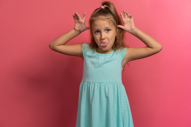 Маленькая красивая детская девочка в голубом платье корчит лица на розовом фоне