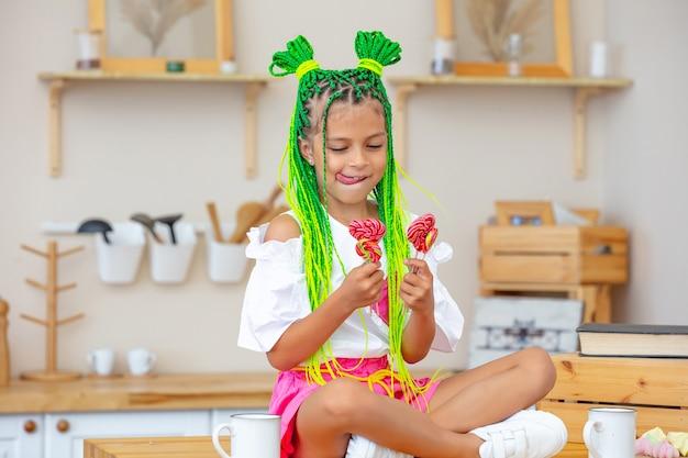 幸せで面白い自宅のキッチンで小さな美しい子供の女の子