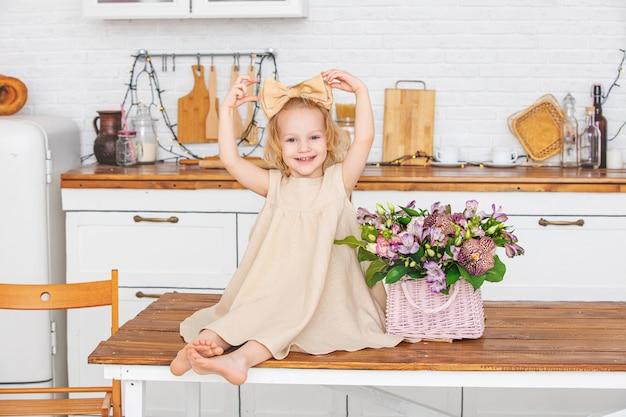 집에서 부엌에서 꽃과 함께 아름 다운 아이 소녀