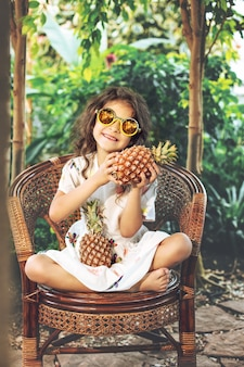 Little beautiful cute baby girl in white dress and sunglasses with pineapples in hands