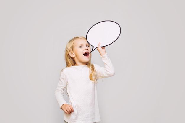 회색 배경의 스튜디오에 있는 표지판의 형태로 생각의 흰 구름을 가진 작고 아름다운 아기 소녀