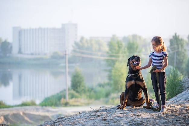 Little beautiful cute girl and a big adult rottweiler dog, sitting on the edge of a sandy cliff hugging and enjoying a warm summer morning in a dense spruce forest
