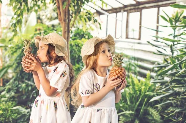 열대 식물에 파인애플을 손에 든 하얀 드레스를 입은 작고 귀여운 소녀들