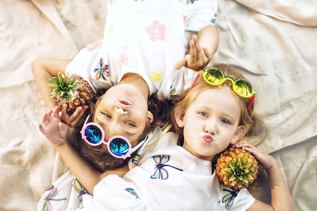 Little beautiful cute girls kids in white dresses with pineapples in hands on tropical plants