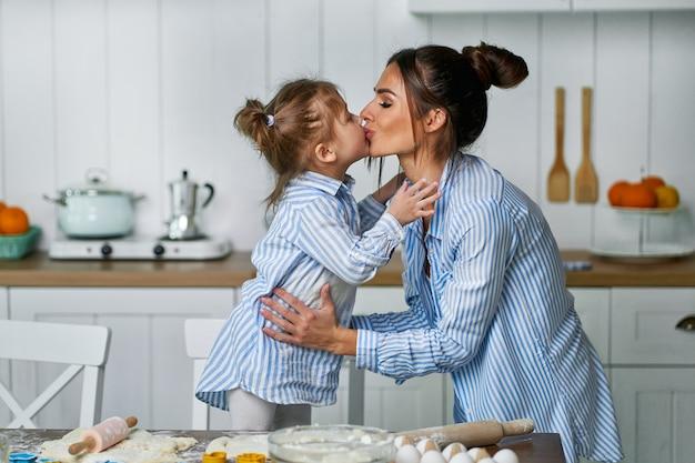 小さな美しい娘がお菓子を調理しながらキッチンで彼女のお母さんにキスします