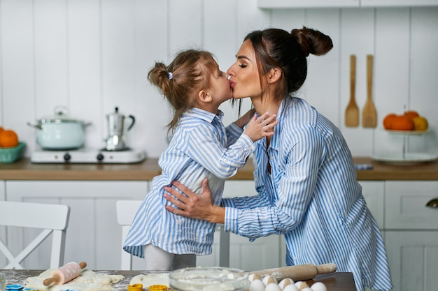 Little beautiful daughter kisses her mom in the kitchen while cooking sweets