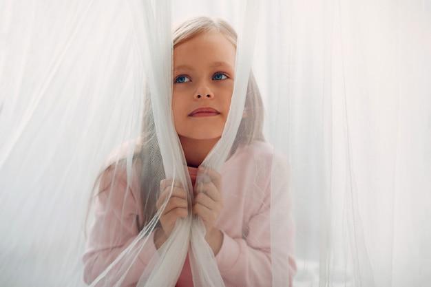 Маленький красивый мечтательный портрет девушки за занавеской в спальне