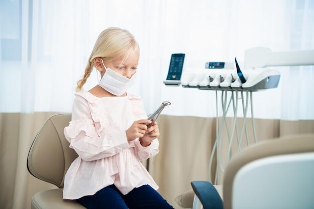 Маленькая красивая девочка у стоматолога, изучив какой-то медицинский инструмент