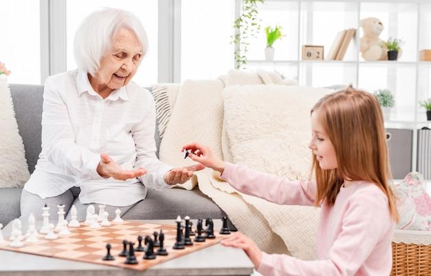 小さな美しい少女と彼女の古い祖母は笑顔でチェスの駒の色を選んでいます