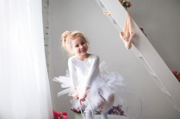 Маленькая красивая девушка и пуанты возле окна.