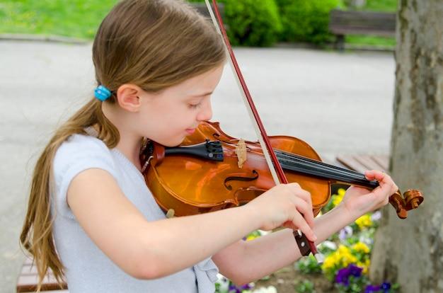 봄 날에 공원에서 작은 아름 다운 여자 busker 재생 바이올린