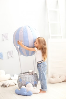 Little beautiful girl in casual clothes stands on a decorative balloon. the child plays in the children room. the concept of childhood, travel. birthday, holiday decorations interior