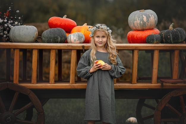 화려한 호박이 든 나무 카트를 든 아름다운 소녀 아이