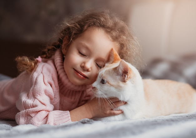 Little beautiful girl cuddles with cat gum on bed
