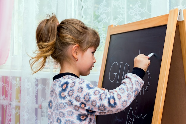 Little beautiful girl drawing on a blackboard.