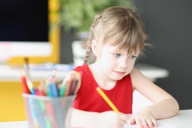 어린 아름다운 소녀는 연필로 어린이 개념의 미세 운동 기술 개발을 그립니다.