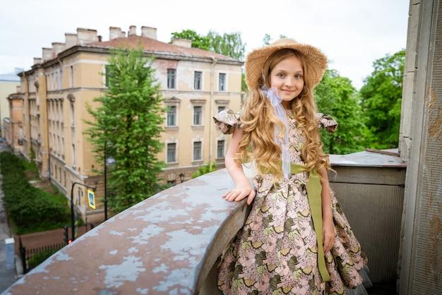 Little beautiful girl in dress on balcony
