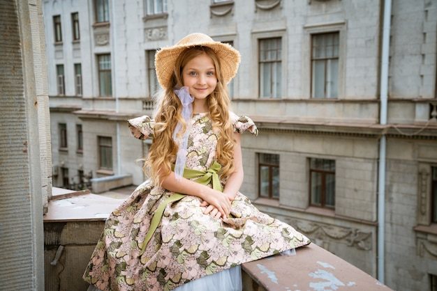 Little beautiful girl in dress and hat posing on the balcony against the scene of the city