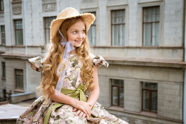 Little beautiful girl in dress and hat posing on the balcony in the city