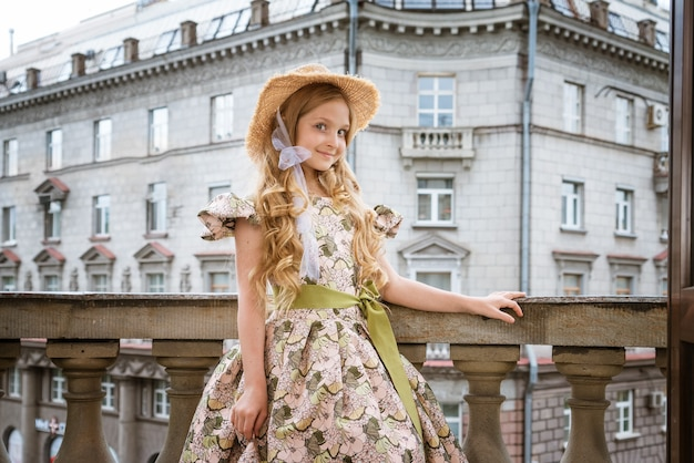 Little beautiful girl in dress and hat posing on the balcony in the street
