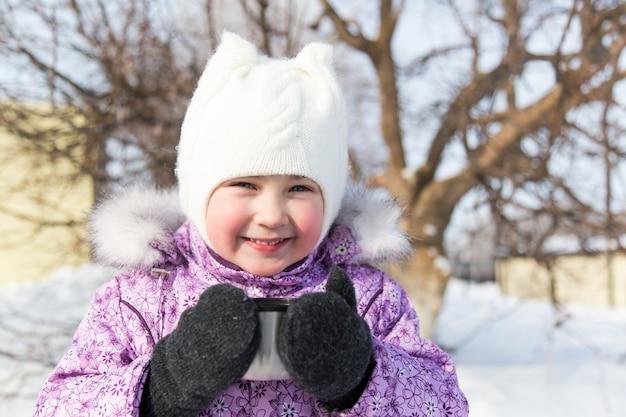 Little beautiful girl drinks tea in the street in winter.