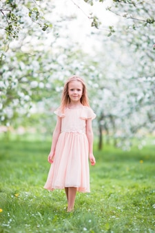 Little beautiful girl enjoying smell in a flowering spring garden