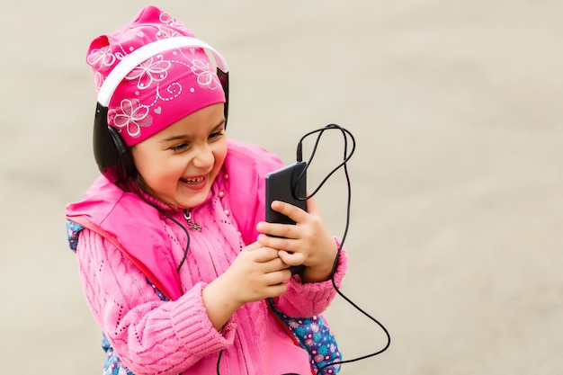 Little beautiful girl enjoys the phone. she headphones. kids and technology