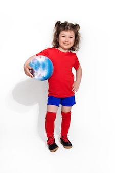 Little beautiful girl in football uniform and with ball in her arm