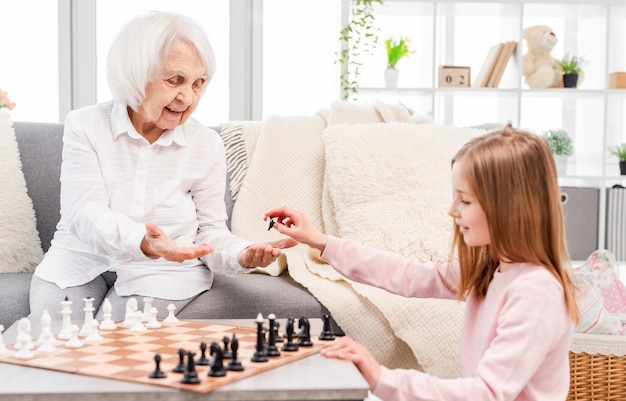 Little beautiful girl and her old grandmother smiling and choosing chess pieces color