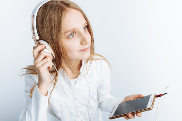 Little beautiful girl holding a smartphone and listening to music, white wall