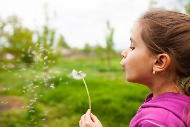 Маленькая красивая девочка держит в руке весенний одуванчик