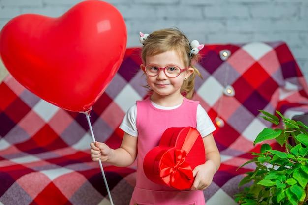 赤いギフトボックスのハートと風船とメガネの少女。バレンタインデーの休日。