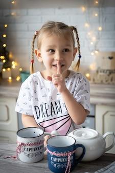 잠옷을 입은 아름다운 소녀가 식탁에 찻잔과 컵을 들고 침묵의 몸짓을 한다
