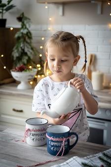잠옷을 입은 아름다운 소녀가 식탁에 있는 컵에 찻주전자에서 차를 붓는다