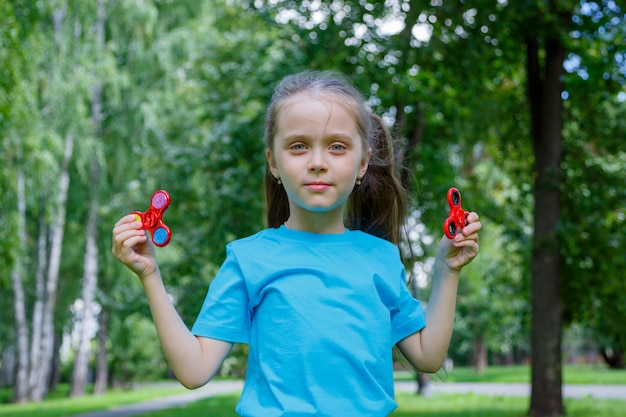 아름 다운 소녀 손에 두 스피너와 놀고있다