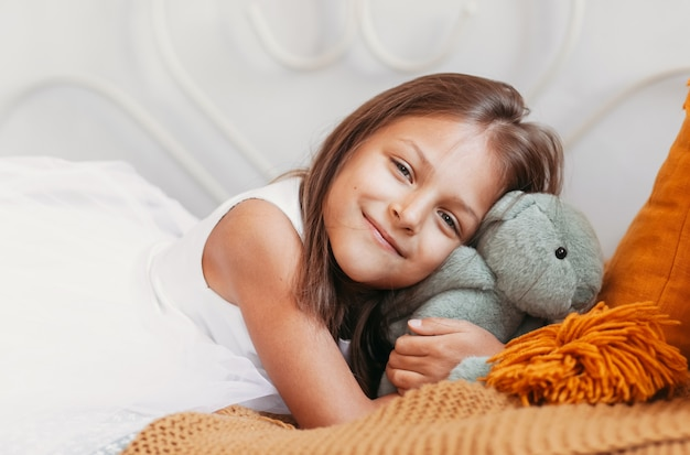 Little beautiful girl lies on a bed and hugs a soft teddy hare