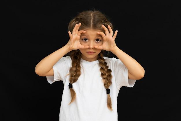 아름 다운 소녀는 검정색 배경에 포즈를 좋아합니다.