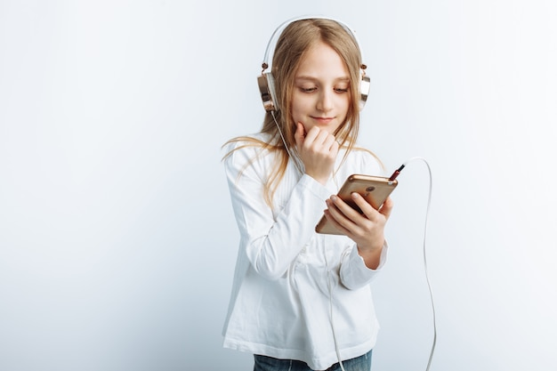 Little beautiful girl, listening to music and looking at the phone