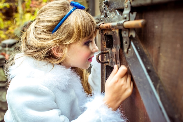 Little beautiful girl looking into the keyhole of the gate
