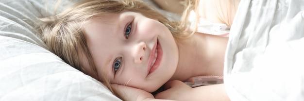 엄마와 함께 침대에 누워 있는 아름다운 소녀