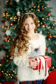 Little beautiful girl model near the christmas tree holds a new year's gift in a red box. close-up portrait.